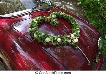 Flower bouquet in heart shape on oldtimer car