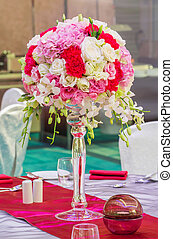 Flower bouquet in glass vase on dining table