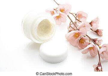 Flower branch with skin cream on white background