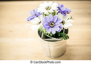 Flower can on wooden table.