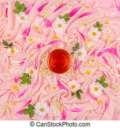 flower composition of white and pink flowers and and a Cup of tea on a pink cloth background, top view flat lay