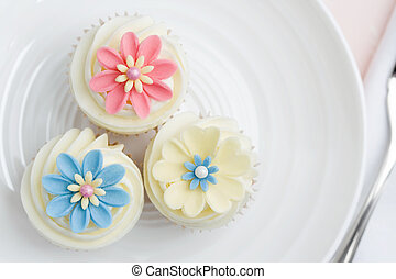 Three flower cupcakes on a white plate