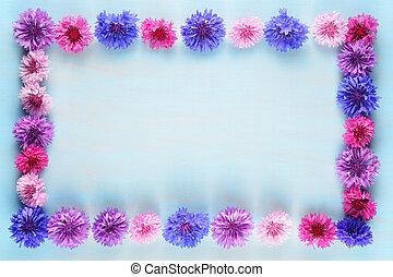 Flower frame of cornflowers on blue background
