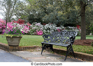 flower garden background behind a wrought iron bench