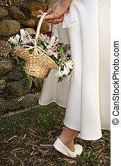 A flower girl showing off her dress, basket and shoes