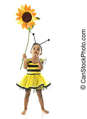 """An adorable 2 year old """"bumble bee"""" looking up in awe at the large sunflower she holds. On a white background."""