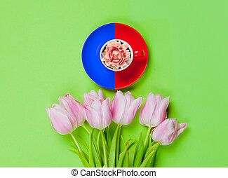 flower in cup and bunch of beautiful tulips on the wonderful green background