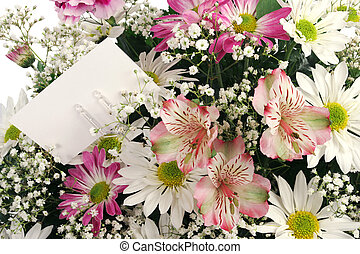A closeup of a bouquet of spring flowers with a gift card.