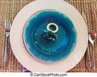flower napkin ring on blue plate