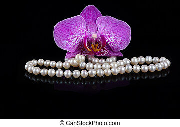 Flower of a pink orchid with beads made from pearls on a black background.