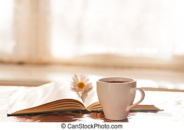 flower on the book, the Cup of black coffee in front of the window in the morning