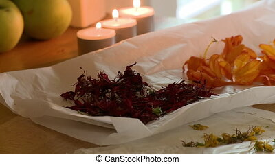 Handheld, close up shot of flower petals and dandelion heads on a napkin next to lit candles.