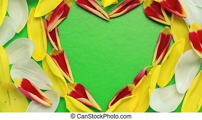 Flower petals flying heart shaped in green background