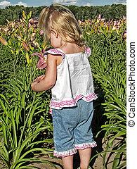 Flower Picker - Little girl picking a flower in a field.