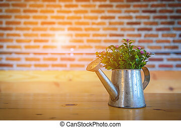 Flower pot on wooden table with blurred red brick wall.