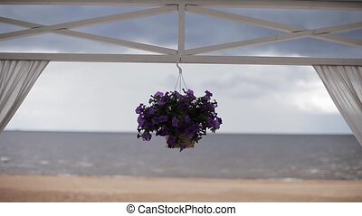 Flower pot with violets suspend on horizontal bar of entry. Coast on background