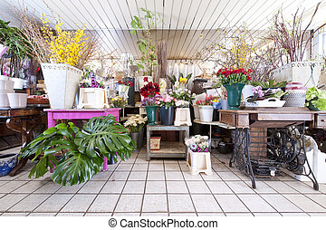 Interior of a flower shop with lots of different country styled objects and flowers