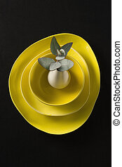 Flower vase kept on porcelain crockery on black background
