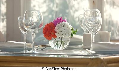 Flower vase on dining table. Side view of shiny wineglasses....