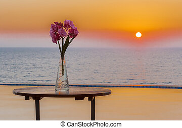 Flower vase on table by pool overlooking sea at sunset