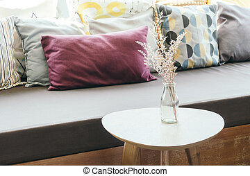 flower vase on table decoration with pillow and sofa