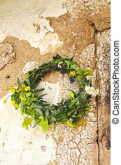 Flower wreath on the wall of old ha