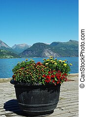 Flowerbed on the pier on beautiful mountain landscape background