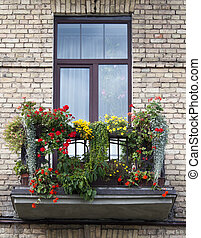 Flowered balcony - Balcony of the brick residential building...