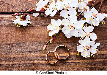 Flowering branch with white delicate flowers on wooden surface. Wedding rings. Wedding bouquet background.