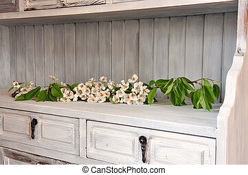 Flowering pear branch in an old shabby chic cabinet.