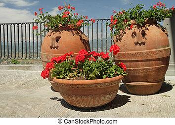 flowering red geranium plants in retro terracotta planters standing on balcony, Italy, Europe
