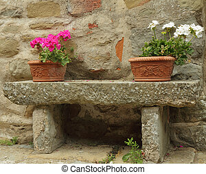 flowerpots with colorful geranium plants in ceramic boxes on stone bench, Tuscany
