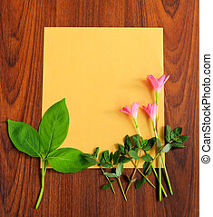 Flowers and leaves with yellow paper on wooden background