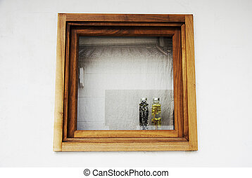 Flowers and plant in the two bottles on wooden box window