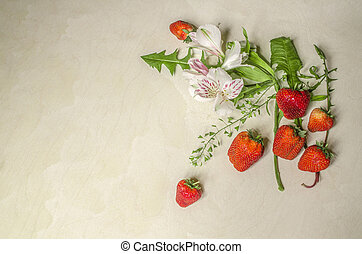 Flowers and ripe strawberries on white plywood