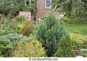 Fine flowers and ornamental shrubs near an accurate rural cottage.