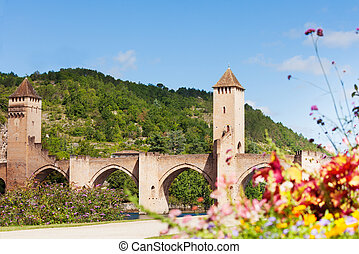 Flowers and Valentre bridge in Cahor, Lot river