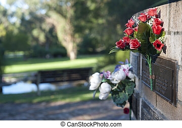 Flowers at grave in cemetery - Colourful flowers as...