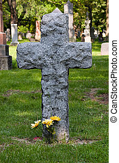 Flowers at a cross-shaped tombstone