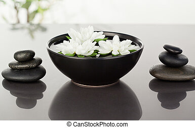 Flowers floating surrounded by stacks of black pebbles