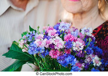 Flowers for a beautiful elderly woman. Focus on the bouquet.