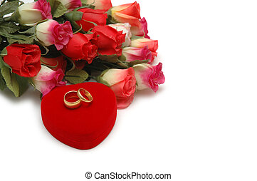 Flowers, heart-shaped box and wedding rings isolated on white