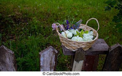Flowers in a basket on an old fence against a background of green grass