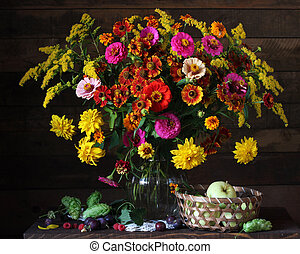 Flowers in a glass vase, apples and berries on the table.