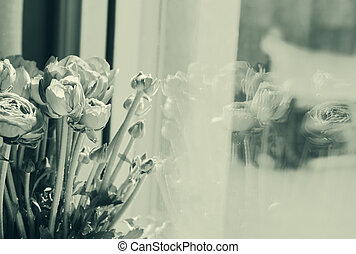 flowers in a glass vase by the window