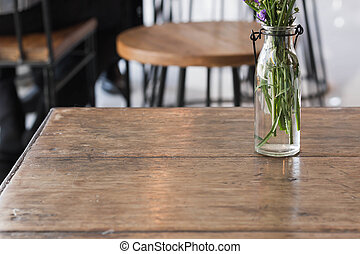 Flowers in a glass vase on a wooden table.