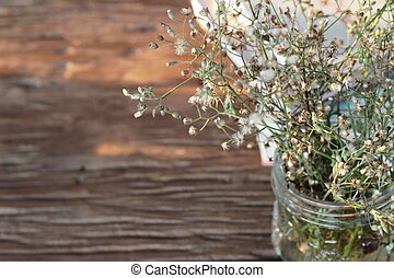 Flowers in a vase on wood background.