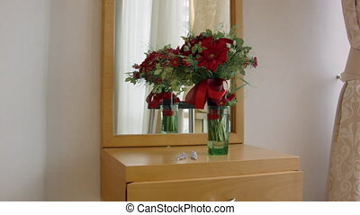 flowers in a vase standing on a dressing table with mirror