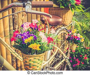 Flowers in basket hanging at bicycle handlebars