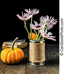 Flowers in krafted vase with pumpkin and old books